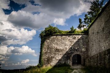 Festungsmauer mit halb geöffnetem Tor bei dramatischem Licht