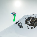 Snowboarder jumping in mountains