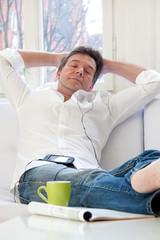 Mann entspannt mit Musik auf dem Sofa