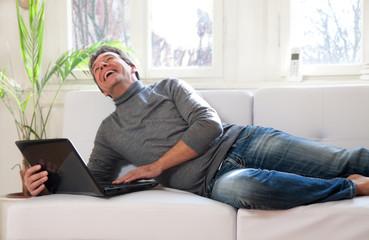 Mann mit Laptop Zuhause auf dem Sofa liegend