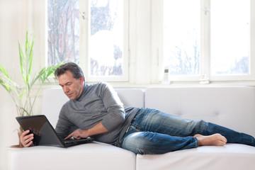 Mann auf dem Sofa liegend im Home Office