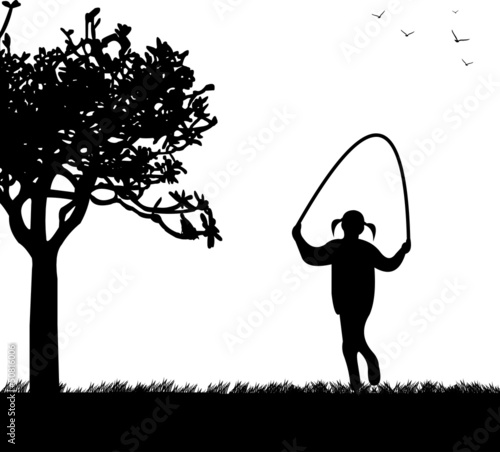A little girl playing skipping rope in park in spring silhouette