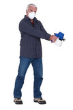 Tradesman holding a spray gun and wearing a mask