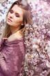 beautiful blonde girl in spring cherry garden