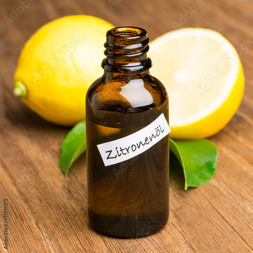 Zitronenöl auf Holz mit Zitronen
