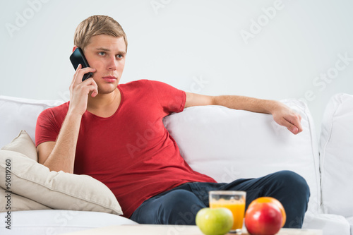 Serious young man sitting on sofa and calling with his smart pho