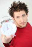 Young man holding an alarm clock