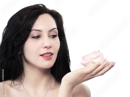 Pretty young woman looking at a rose - isolated
