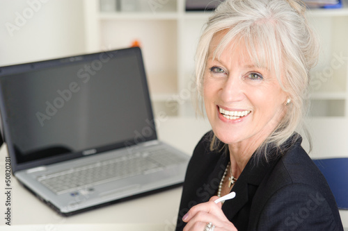 Portrait einer attraktiven älteren Geschäftsfrau am Schreibtisch