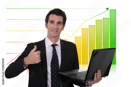Businessman giving the thumbs-up whilst standing by bar chart