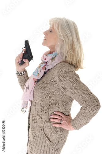 Attraktive Seniorin hält eine Pistole
