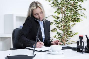 Geschäftsfrau telefoniert und macht sich Notizen im Büro