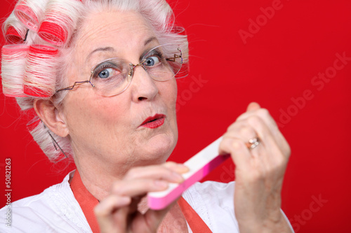 Elderly woman filing her nails