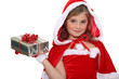 Little girl in a Santa costume with a wrapped gift