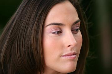 Pensive brunette outdoor head-shot