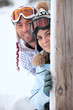 young couple at ski resort hiding behind wooden post