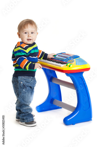 little boy and the keyboard on white background. funny boy baby.