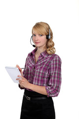 Woman in a headset writing in a notepad