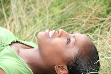 African woman lying on grass
