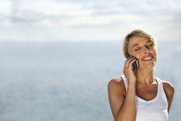 Woman on telephone at the beach