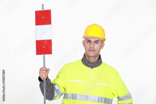 A traffic guard holding up a sign
