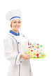 Female chef holding a birthday cake