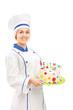 Female chef holding a birthday cake