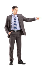 Full length portrait of an angry businessman pointing with his f