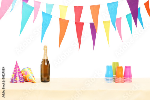 Bottle of sparkling wine, plastic glasses and party hats