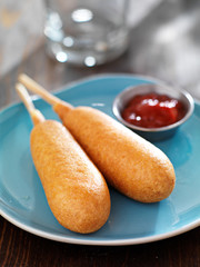 two corn dogs on a plate with ketchup