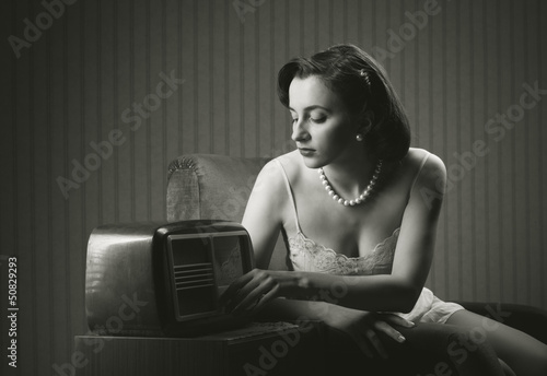 Sensual woman listening music on old radio
