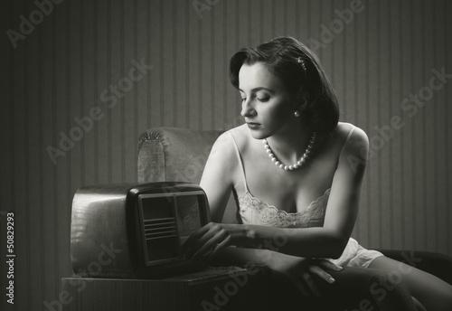 Sensual woman listening music on old radio