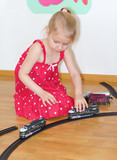 Little girl playing with railway sitting on the floor