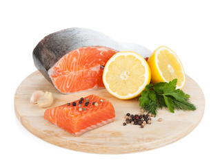 Salmon with herbs and lemon slices on cutting board
