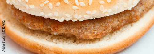 Close-up of burger bun with sesame seeds on white.