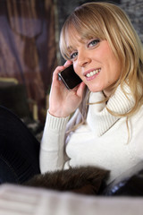 Woman in cosy jumper sat on couch making telephone call