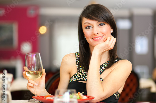 Woman toasting wine in a restaurant