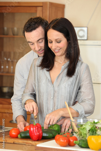 Couple cutting vegetables in a kitchen
