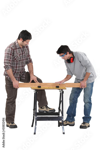 Father and son securing plank of wood