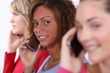 Three women using mobile telephones