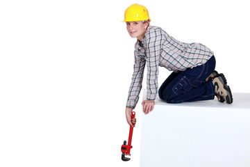 Woman reaching down with a wrench