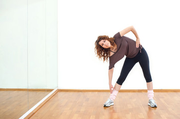 Young woman stretching her leg in the gym.