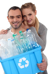 Couple recycling caret of plastic bottles