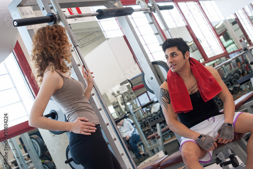 Young friends talking at the gym while training.