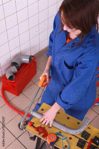 Female plumber sawing pipe