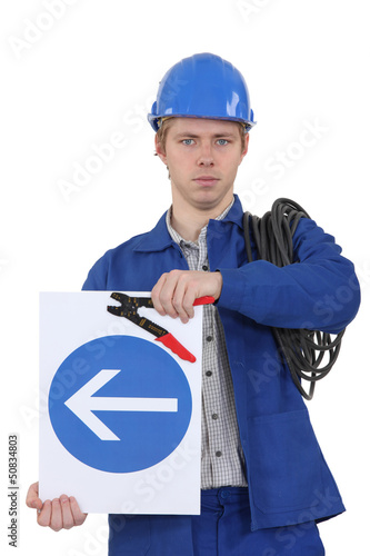 Electrician with a one way sign
