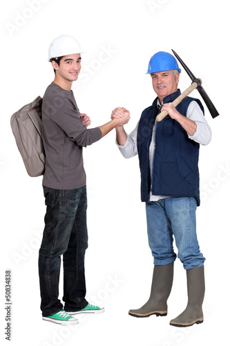 apprentice and senior bricklayer isolated on white