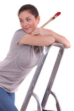 Woman holding paint brush whilst climbing ladder