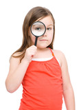 Cute little girl is looking through magnifier