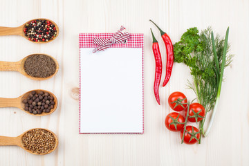Recipe or menu book, chili, tomatoes, spices on wood